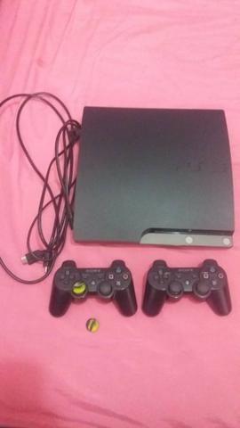 PS3 Slim na caixa com 2 controles, carregador, e 24 jogos