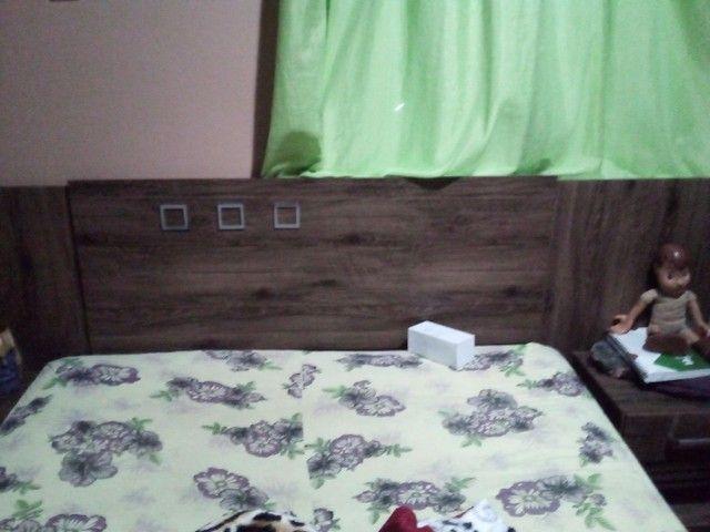 Um painel  de TV e um cabeceira de cama  e um tv de 32