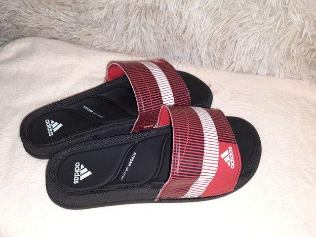 9 8 6 0 0 - 1 0 2 1 * Chinelo slide Adidas preto vermelho  - Foto 2