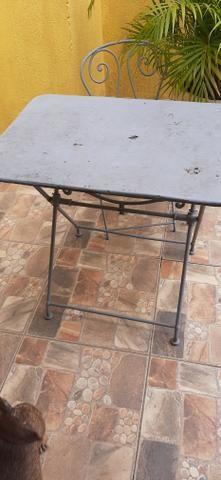 Mesa de ferro em pernas arrematadas em trava com uma cadeira