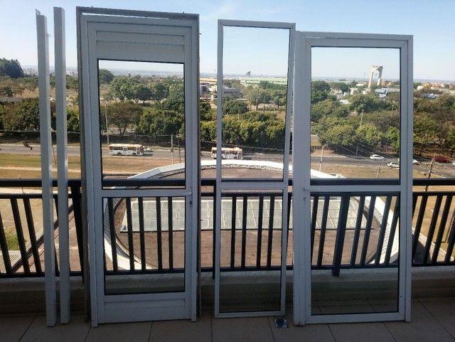Conjunto de duas portas mais uma porta fixa, com vidros.