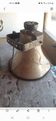 Um alto falante e um caldeirão grande usado para fazer pamonha