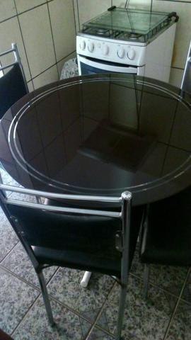 Mesa de vidro semi nova com 4 cadeiras revestidas de couro cintetico