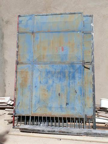 Portão de ferro, com trilhos.