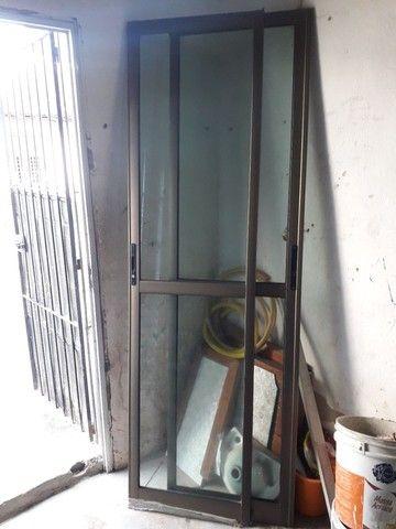 Porta e janelão de alumínio, bronze e vidro.