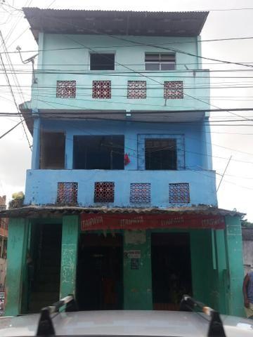 Um predio com tres casa um ponto comercial e uma cobertura