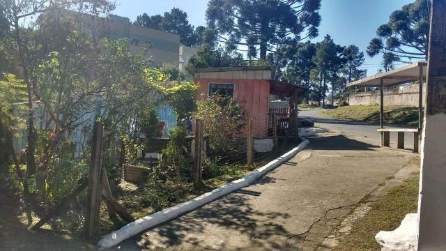Terreno de esquina com casa de madeira