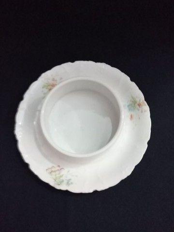 Mantegueira de porcelana com desenho de flores.
