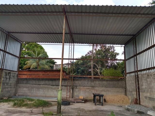 Casa com terreno murado e galpão