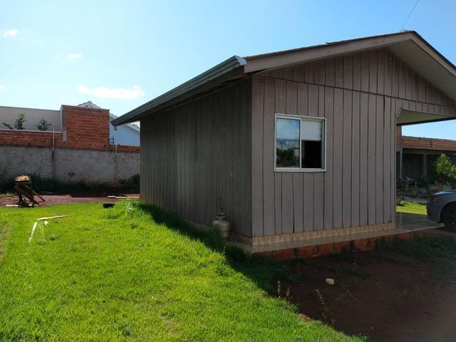 Terreno murado com casa de madeira