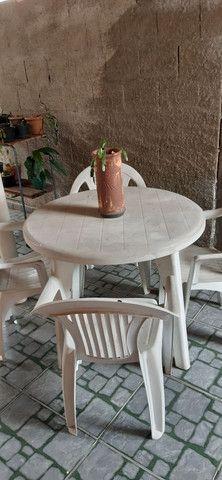 Mesa com quatro cadeiras de plástico