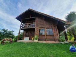 Sitio com casa central de madeira e muita