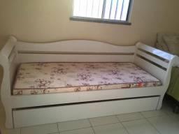 Cama de solteiro com colchão e cama auxiliar.