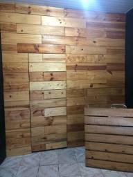 Parede de madeira com porta, arara de parede e balcão de madeira