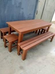 Mesa de madeira com bancos e tamboretes