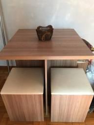Mesa com 4 bancos baú, com pequenos detalhes de uso
