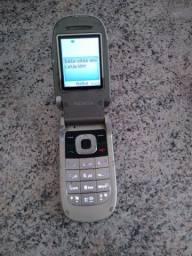 Celular Nokia antigo com carregador.