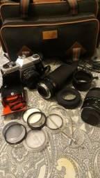 1 Câmera Pentax K1000 + 3 Lentes + 10 Filtros + Maleta de transporte + 2 pilhas + Manuais