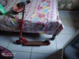 Bicicleta preta com detalhes rosa de criança e um patinete de criança