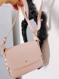 Bolsa rosé com tachas nas laterais e alça regulável