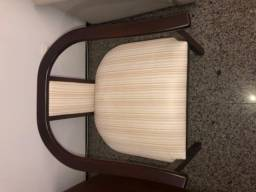 Cadeira de madeira escura com estofado claro.