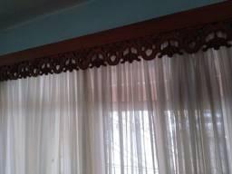 Aparador de madeira e cortina trabalhado tem outro do outro lado o jogo