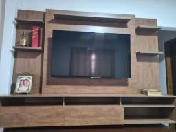 Painel de televisão com prateleiras e portas deslizantes.
