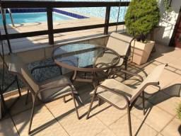 Mesa redonda com quatro cadeiras em ferro e vidro para área externa.