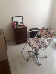 Cadeira 2 pufes, um espelho redondo, um móvel,  e um lavatório portátil.