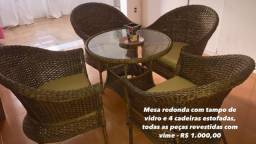 Mesa com tampa de vidro e cadeiras revestidas de vime
