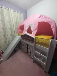 Cama infantil com escorregado, cabana e cortina.