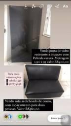 Porta de vidro e sofá aconchegante de couro
