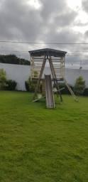 Parque de madeira com.gangorra e escorrega