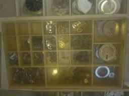 Estojo com peças de relógio.
