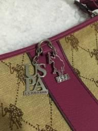 Linda bolsa US Polo ASSN pequena. Cor em tom magenta e bege