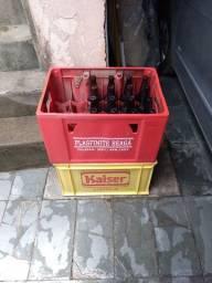 Dois vasilhames com quarenta garrafas cerveja.