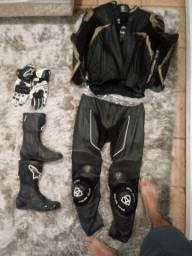Equipamento proteção pra moto; macacão, bota, luva e capacete vermelho.