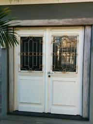 Porta de madeira antiga com vidro decorado e grade de ferro