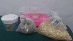 Gaiola rosa para hamster com pó de banho, serragem e sementes.
