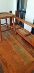 Mesa de madeira de demolição com três cadeiras e um banco.