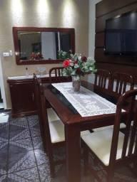 Mesa de jantar com seis cadeira um balcão e o espelho