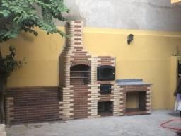 Banco, churrasqueira, forno e bancada de tijolos coloniais de cor mesclada