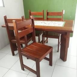 Mesa de madeira maciça com 4 cadeiras e tampo decorado.