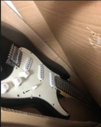 guitarra zebra modelo stratocaster com caixa amplificadora com distorção