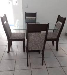 Mesa de vidro com quarto cadeiras