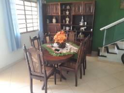 Uma estante e uma mesa com 6 cadeira