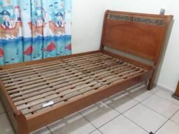 Cama de madeira com colchão de molas.