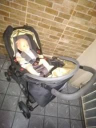 Carrinho de bebê com bebê conforto acoplado.