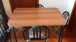 Mesa de madeira marrom retrátil com 4 cadeiras pretas