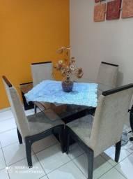 Mesa de jantar com 4 cadeiras estofadas.